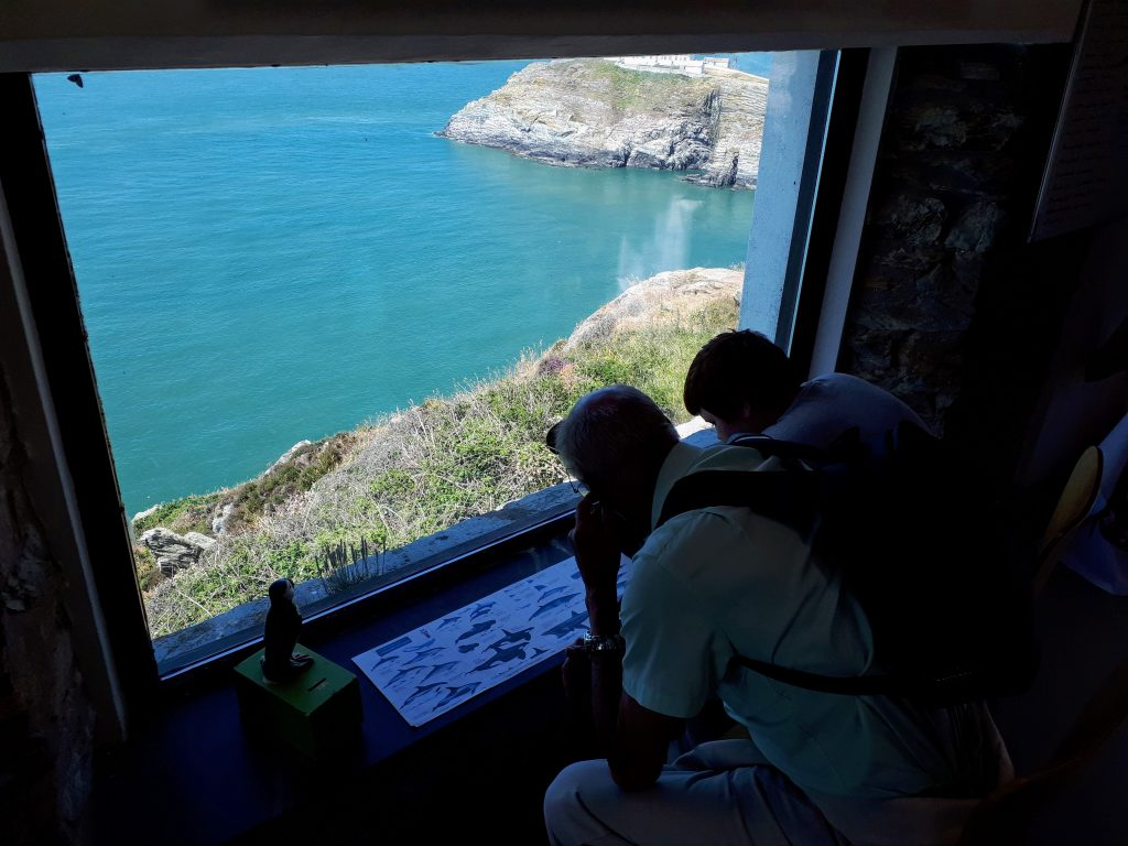 the image shows a bird watching hide at South Stack were you can sit with the free use of binoculars. Informational boards all around.