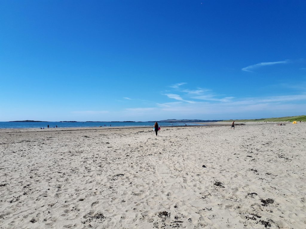 The image shows how big and long Crigyll beach is in summer with only a few people on it.