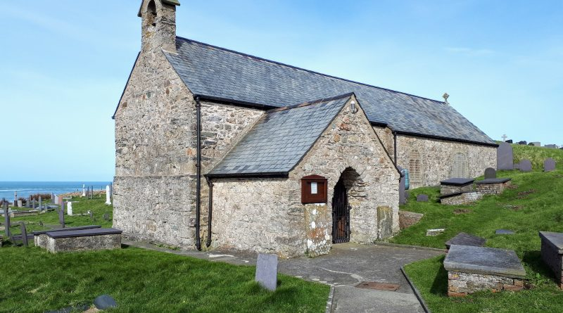 A picture of the front of Llanbadrig Church with the blue sea and sky in the background