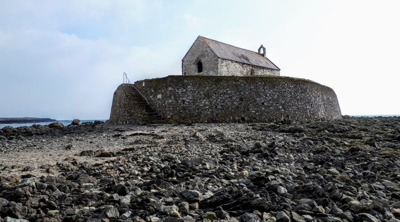 A picture of Cwyfan Church taken at low tide from the rock below