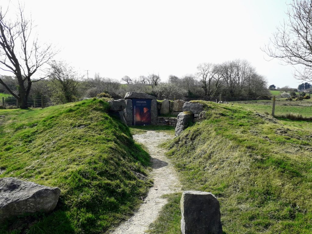 The image shows the information board and mock burial chamber on the car park for Bry Celli Ddu.
