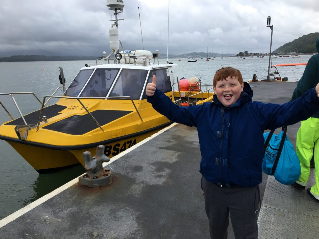 young boy standing next to the fishing boat, he has both thumbs up and a smile on his face