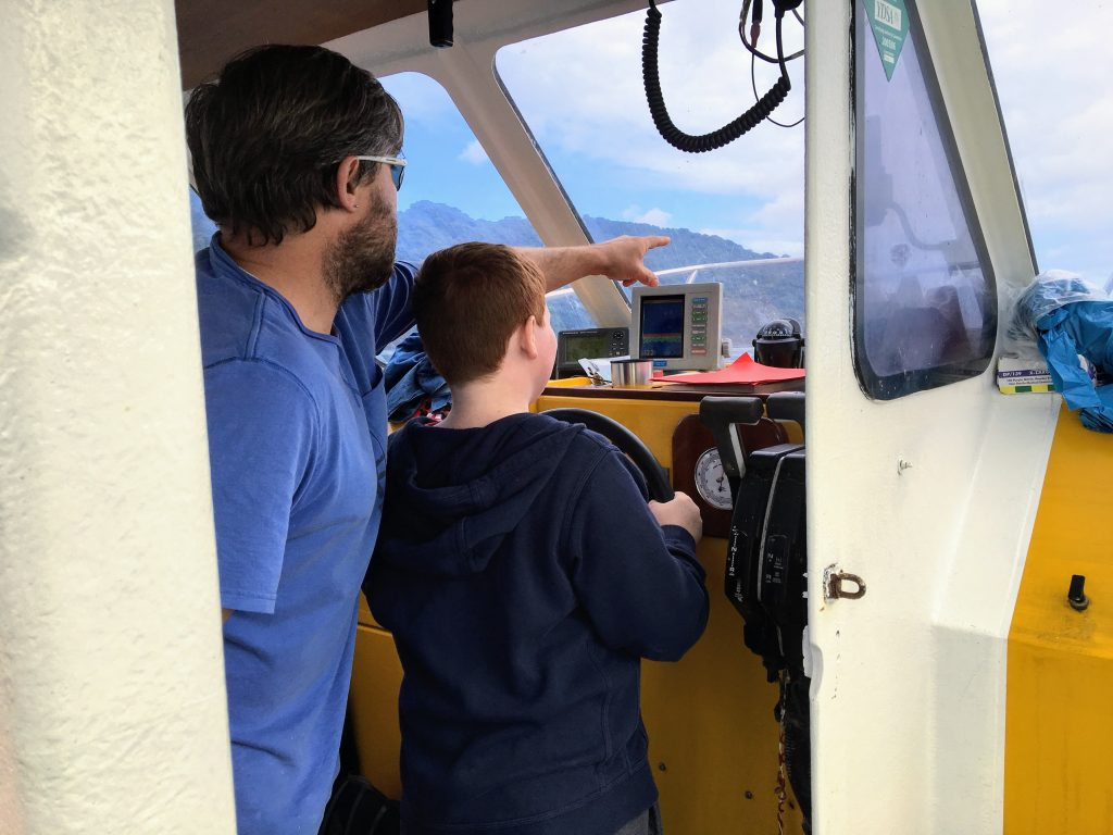 A young boy aboard Starida2 being shown how to steer the boat during a Starida fishing trip