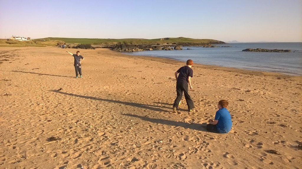 Children playing football in the sun on Tyn Tywyn beach
