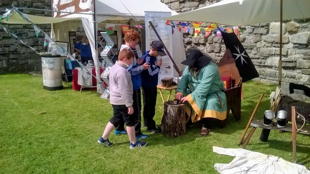 The image shows children gathered around a stall making coins the old fashioned way