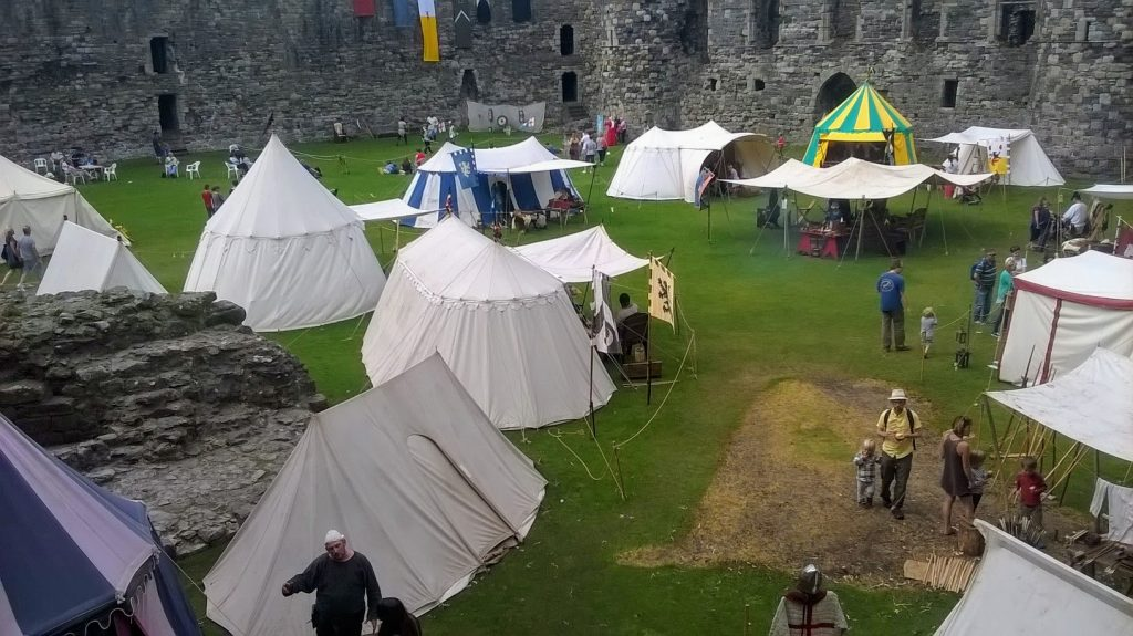 The image shows tents in the courtyard of the castle with various things on display such as weaponary and basket weaving