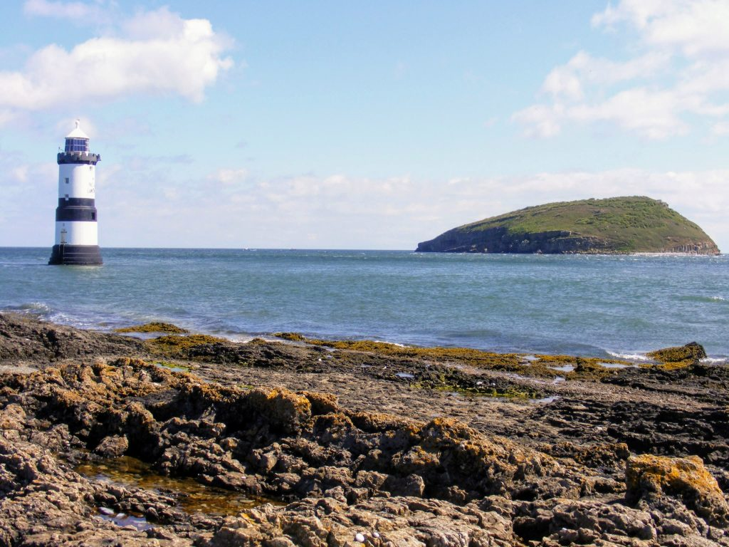 a picture of the lighthouse at Penmon Point with Puffin Island in the background
