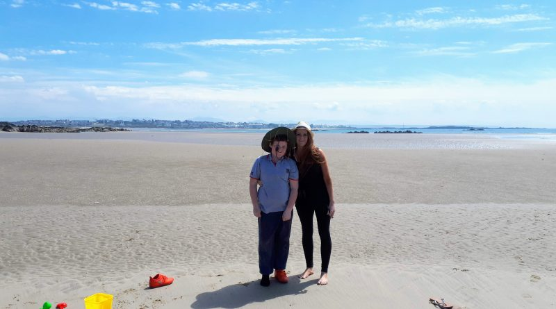 The picture shows two people enjoying the sun on Cymyran beach for free